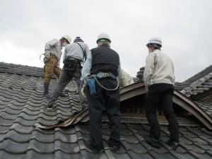 屋根に上がり、換気口に塗る塗料の色を相談します